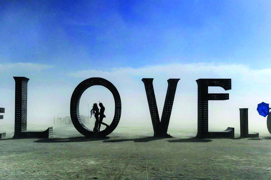 "In this Aug. 30, 2014 photo, a couple stands inside a love sculpture at Burning Man on the Black Rock Desert of Gerlach, Nev. The #MeToo movement is making its way to Burning Man which begins Aug. 26-Sept. 3, 2018. Organizers are reminding attendees that just because the counterculture festival in the Nevada desert is known for occasional nudity and kinky landmarks like the ""Orgy Dome,"" it doesn't mean it's a free-for-all when it comes to touching or non-consensual sex. (Andy Barron/The Reno Gazette-Journal via AP)"